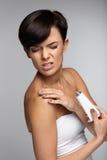 伤害治疗 充满胳膊痛苦的美丽的妇女,应用奶油 免版税库存图片