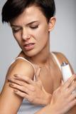 伤害治疗 充满胳膊痛苦的美丽的妇女,应用奶油 免版税库存照片