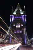 伦敦、英国、塔桥梁在晚上与公共汽车轻的足迹和汽车在桥梁,长的曝光在低灯射击了 免版税库存照片