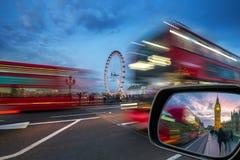 伦敦、议会英国-偶象红色双层汽车在活动中在有大本钟的威斯敏斯特桥梁和议院  库存照片