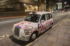 伦敦与给油漆工作做广告的出租车 库存照片