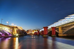伦敦与老和新的桥梁的晚上都市风景 免版税库存图片