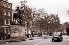 伦敦出租车和老大厦 免版税图库摄影