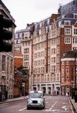 伦敦出租车和老大厦 库存照片