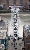 伦敦千年在通过走泰晤士河和办公室的人民的脚桥梁 图库摄影