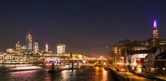 伦敦地平线在与泰晤士河、桥梁,城市大厦和河船横渡的晚上 免版税库存图片
