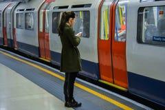 伦敦地铁-女孩等待的火车 免版税库存图片