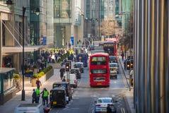 伦敦市,金丝雀码头与走的商人和运输lols的街道视图在路 事务和现代生活o 免版税库存照片