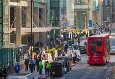 伦敦市,金丝雀码头与走的商人和运输lols的街道视图在路 免版税库存照片