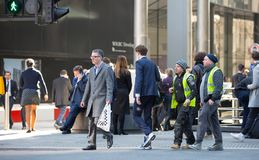 伦敦市,金丝雀码头与走的商人和运输lols的街道视图在路 免版税图库摄影