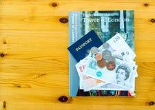 伦敦旅行书、美国护照和英国金钱在桌上 库存照片