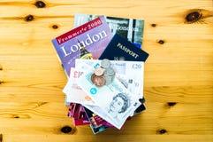 伦敦旅行书、美国护照和英国金钱在桌上 库存图片