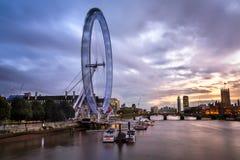 伦敦眼和威斯敏斯特桥梁在晚上,英国 免版税库存照片