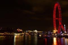 伦敦眼睛和泰晤士河风景夜视图的从威斯敏斯特桥梁 免版税库存图片
