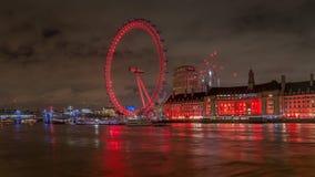 伦敦眼睛点燃了与五颜六色的光在从威斯敏斯特桥梁的晚上在泰晤士河 库存照片