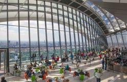 伦敦,人们在天空庭院携带无线电话大厦的餐馆 库存照片