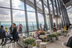 伦敦,休息和享受伦敦全景的天空咖啡馆的人们 库存图片