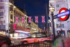 伦敦,英国,英国:2017年6月16日-与旗子英国国旗的普遍的游人Picadilly马戏在夜点燃illuminatio 图库摄影