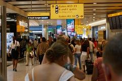 伦敦,英国, 7月03日 2009年:走往A13-23门的许多乘客在希思罗机场中 另外方向和广告 免版税库存照片