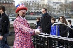 伦敦,英国:2018年3月8日:在英国旗子夹克打扮的一个人和太阳镜和卖票的`伦敦`帽子外面 免版税图库摄影