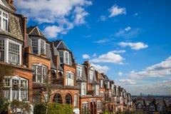 伦敦,英国-传统砖房子和舱内甲板在与蓝天和云彩的一个好夏天早晨 库存照片