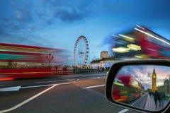 伦敦,英国-偶象红色双层汽车在活动中在有大本钟的威斯敏斯特桥梁 库存图片