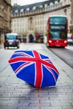 伦敦,英国-在摄政的街道的英国伞有偶象红色双层汽车和黑出租汽车的 库存图片