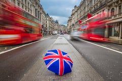 伦敦,英国-在繁忙的摄政的街道的英国伞有偶象红色双层汽车的 免版税库存照片