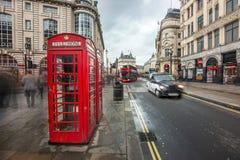 伦敦,英国- 15 03 2018年:在皮卡迪利广场附近的偶象红色电话亭有红色双层汽车的 免版税库存照片