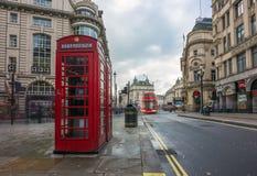 伦敦,英国- 15 03 2018年:在皮卡迪利广场附近的偶象红色telehone箱子有红色双层汽车的 免版税库存图片