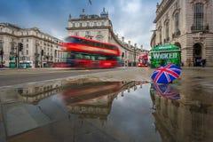 伦敦,英国- 03 15 2018年:红色双层汽车的反射在活动中在有英国伞的皮卡迪利广场 免版税图库摄影