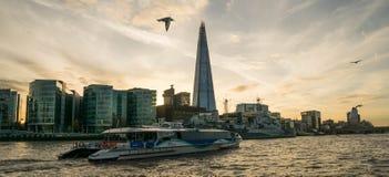 伦敦,英国- 2017年10月17日, :从泰晤士河沿的碎片大厦视图与河游轮视线内,日落 库存照片