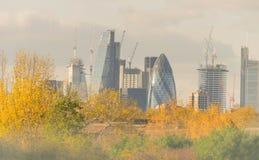 伦敦,英国- 2017年10月17日, :伦敦现代商业区在与顶上喷气机的飞行的一清楚的天空天 免版税图库摄影