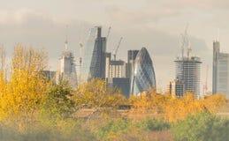 伦敦,英国- 2017年10月17日, :伦敦现代商业区在与顶上喷气机的飞行的一清楚的天空天 图库摄影