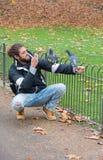 伦敦,英国- 2018年11月24日:一个人在圣詹姆斯公园为鸽子照相 免版税库存照片