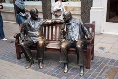 伦敦,英国- 2010年2月25日:人雕塑坐在古铜的长凳 盟友在街道上雕刻 朋友 库存照片