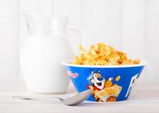 伦敦,英国- 2018年6月01日:凯洛格` s Frosties早餐谷物原始的板材用在白色木头的牛奶 免版税图库摄影