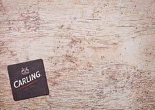 伦敦,英国- 2018年2月04日:在木头的Carling啤酒原始的beermat沿海航船 免版税库存图片