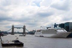 伦敦,英国- 2010年2月25日:在泰晤士河的塔桥梁 在城市码头的船 多云天空的河 库存图片