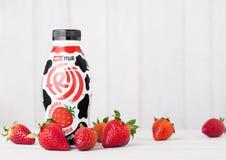 伦敦,英国- 2018年5月03日:塑料瓶研磨器在白色木背景的草莓饮料用新鲜的莓果 库存照片