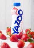 伦敦,英国- 2018年5月03日:塑料瓶Yazoo在木背景的草莓饮料用新鲜水果 免版税库存图片