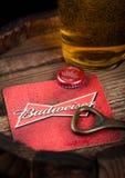 伦敦,英国- 2018年8月10日:百威有瓶上面的啤酒沿海航船和开启者和杯在木桶顶部的啤酒 免版税库存照片