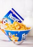 伦敦,英国- 2018年6月01日:箱凯洛格` s Frosties早餐谷物用牛奶和板材在白色木头 免版税库存图片