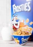 伦敦,英国- 2018年6月01日:箱凯洛格` s Frosties早餐谷物用牛奶和板材在白色木头 免版税库存照片