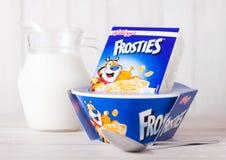 伦敦,英国- 2018年6月01日:箱凯洛格` s Frosties早餐谷物用牛奶和板材在白色木头 库存照片
