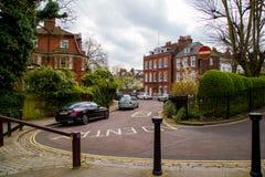 伦敦,英国- 4月, 13日:有维多利亚女王时代的房子的典型的英国街道 免版税图库摄影