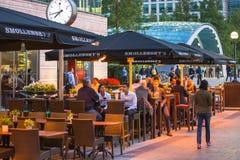 伦敦,英国- 2015年9月7日, :金丝雀码头夜生活 坐在地方餐馆的人们在长时间工作日以后 免版税库存图片