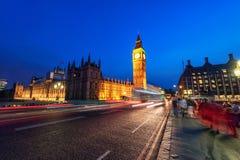 伦敦,英国- 2016年8月18日:伦敦大本钟和有威斯敏斯特宫的威斯敏斯特桥梁 由于长期的模糊的人 免版税库存照片