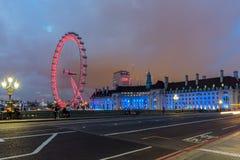 伦敦,英国- 2016年6月16日:伦敦眼和从威斯敏斯特桥梁,伦敦,英国的县政厅的夜照片 免版税库存图片