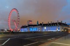 伦敦,英国- 2016年6月16日:伦敦眼和从威斯敏斯特桥梁,伦敦,英国的县政厅的夜照片 库存照片